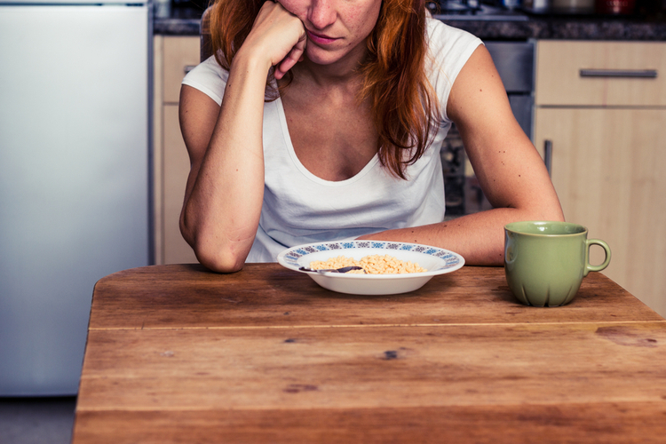 Woman does not want to eat her cereal.