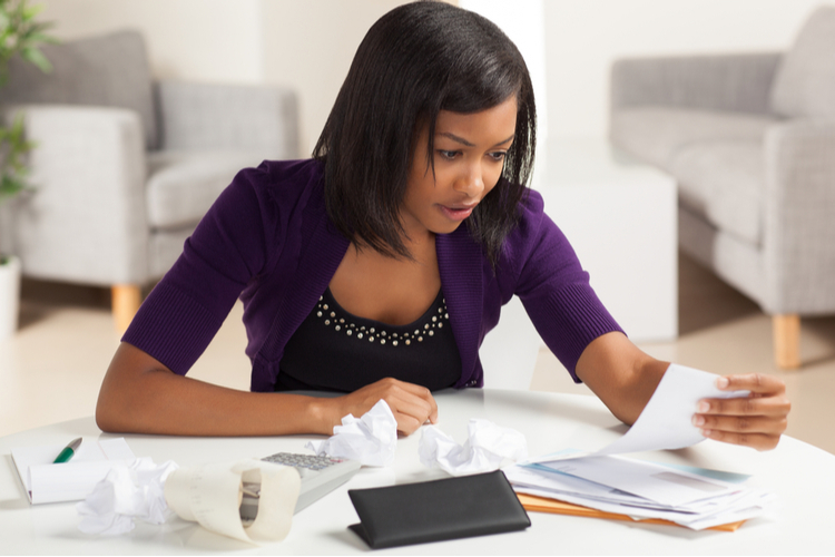 Woman working on finances at home wearing purple jacket sitting at dining table.