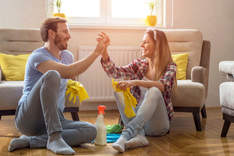 Couple is giving high five and smiling while sitting on the floor in living room after cleaning it.