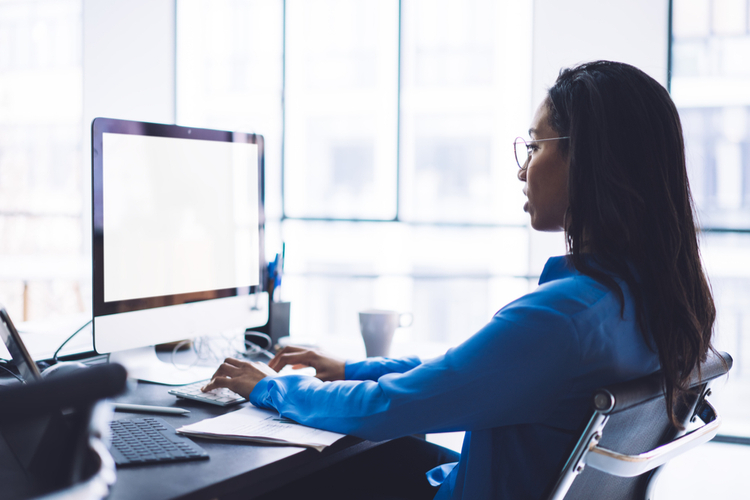 Lady sitting in front of empty screen of monitor.