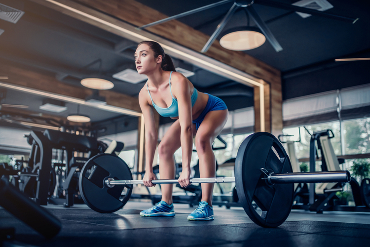Attractive young sports woman with barbell. Deadlift.