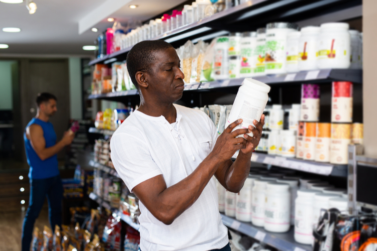 Man reading label carefully before buying in shop.