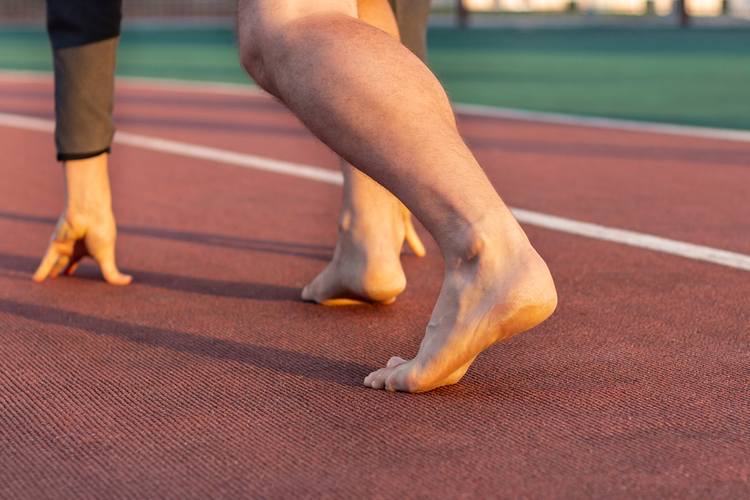 Athlete's legs on a starting position without shoes.