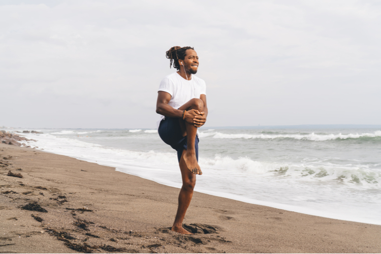 Male athlete in sportswear standing on sandy beach and doing stretching exercise during workout in summer.
