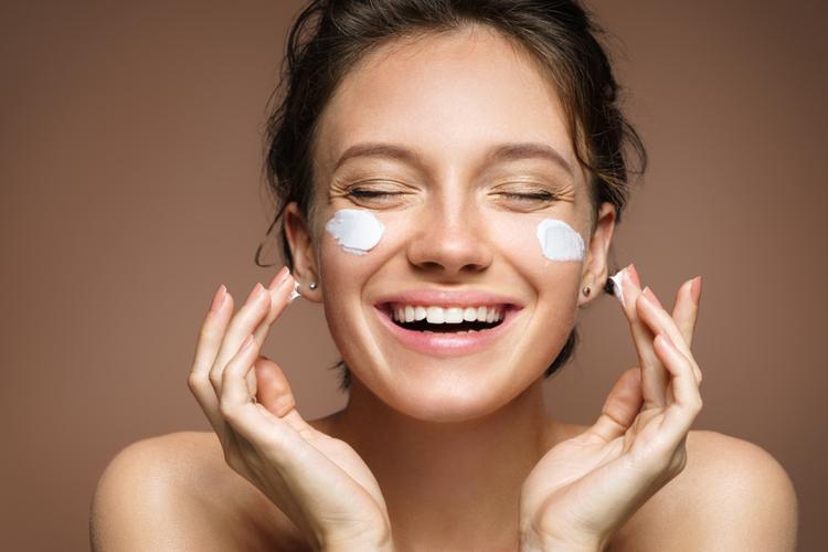 Laughing girl applying moisturizing cream on her face.