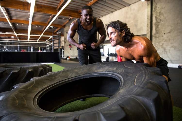 Workout partners scream and shout inspiring each other for motivation during intense extreme session.