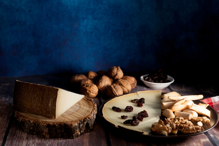 Cheese, raisins and nuts on dish on wood table.
