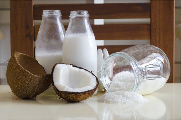 Cracked open coconut with meat cut in half, grounded flakes in a mason jar.