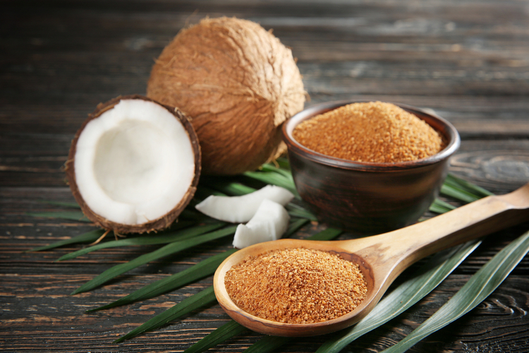 Bowl and spoon of brown sugar with coconut on wooden background.
