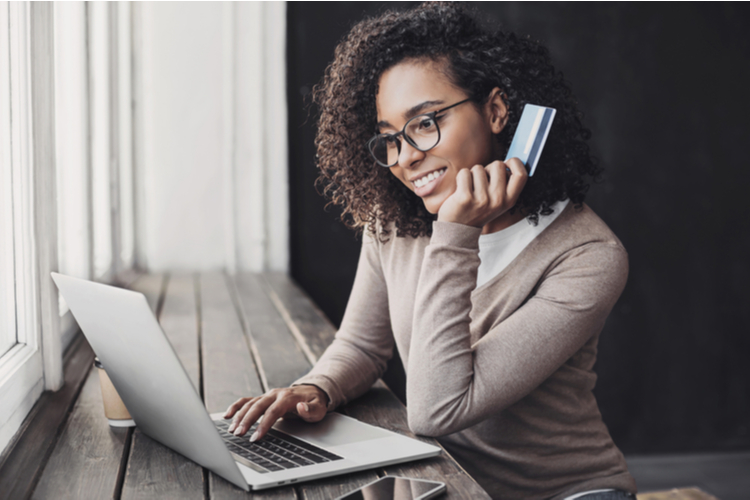 Young woman holding credit card and using laptop making payment online.