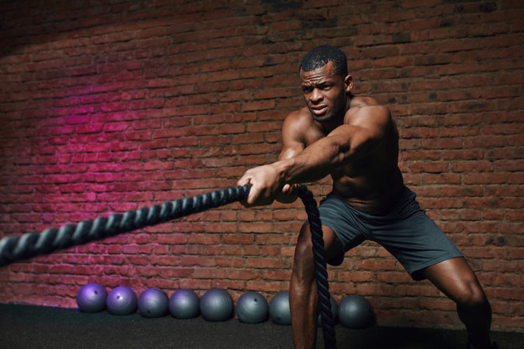 Cross fit coach stands with battle ropes proves that dynamic workout with ropes strengthening athlete's body.