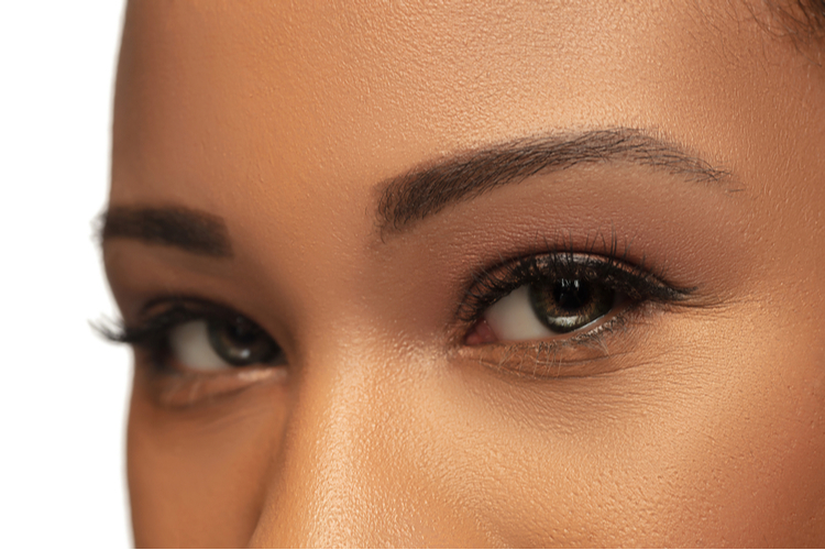 Close up of female eyes with nude make up and bombbrows microshade brow pencil.