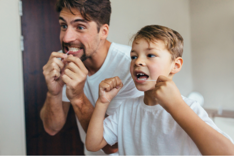 Father and son flossing their teeth in the bathroom.