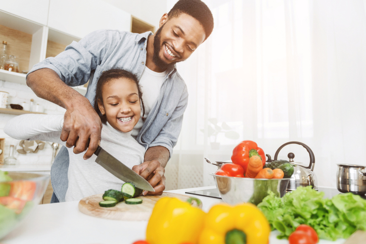 Man teaching his little daughter to cut vegetables.