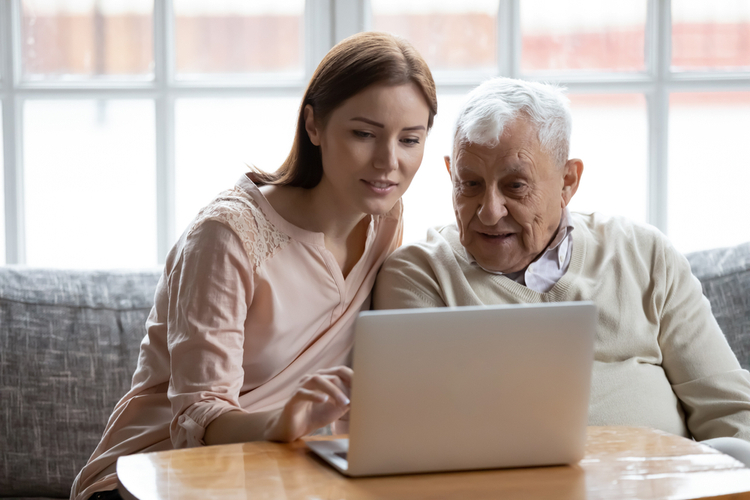 Grown-up daughter and old 80s father choose goods or services via internet or web surfing together at home.