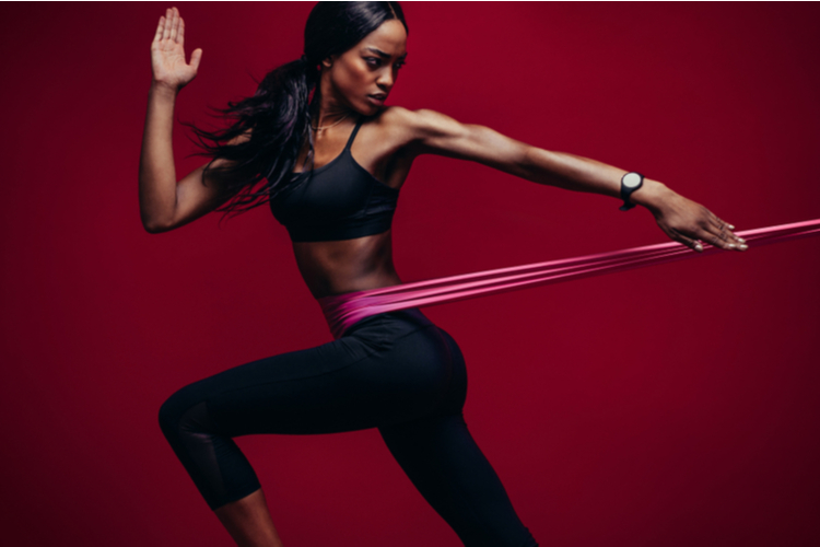 Strong woman using a resistance band in her exercise routine. Female athlete exercising with resistance band in studio.