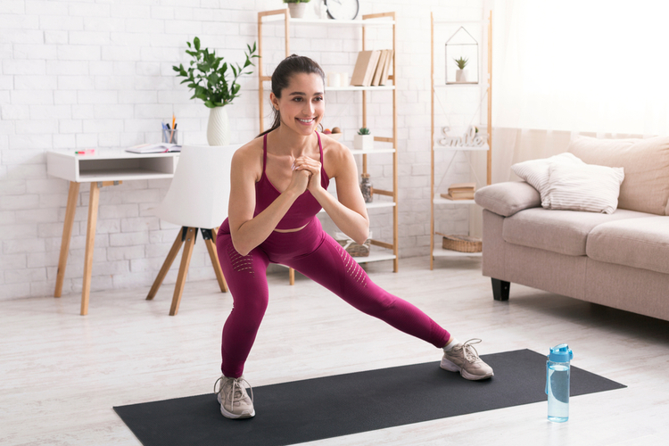 Happy millennial girl doing lunges on yoga mat following the FIIT formula in light room.