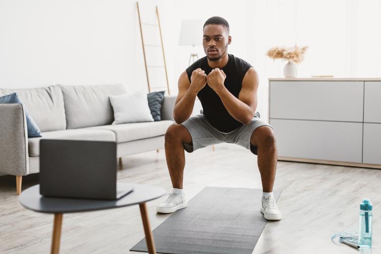 Man doing deep squats looking at laptop.
