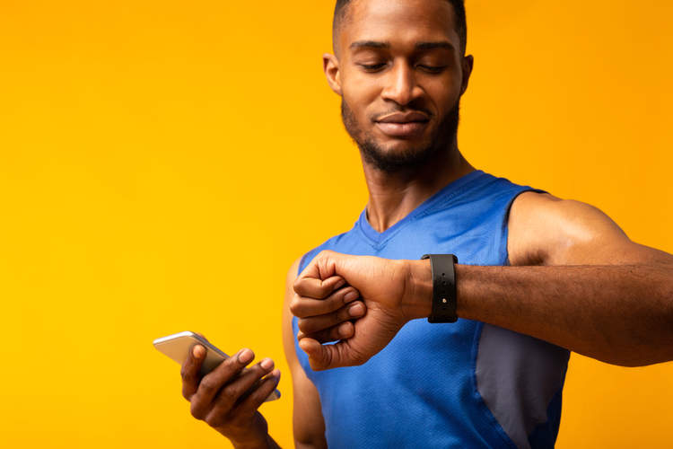 Muscular man looking at smartwatch while holding smartphone.