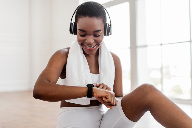 Woman looking at activity fitness tracker smartwatch during workout break to play spotify.