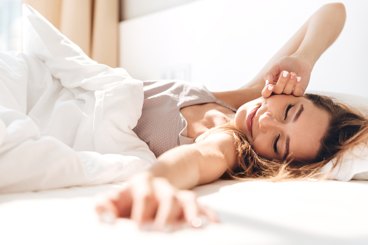 Young woman who is smiling while stretching after waking up from a satisfying sleep.