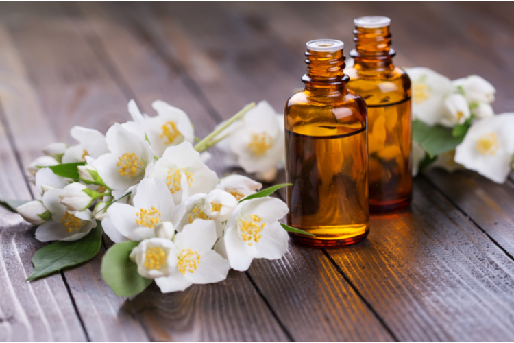 Essential aroma oil with jasmine on wooden background.