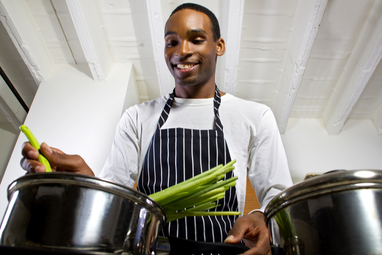 close up of a young black man wearing an apron and cooking at home. he is in a domestic kitchen and preparing a vegetarian meal.