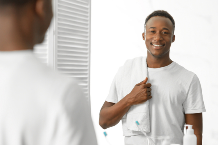 Young man holding a towel going to the shower.