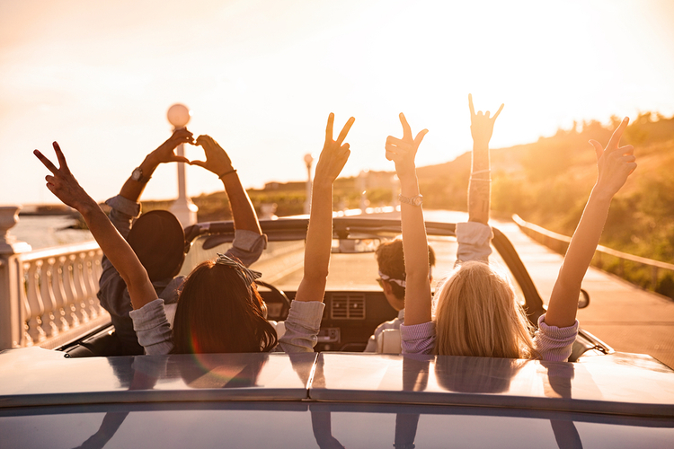 A group of happy people/friends while driving on the road with their hands up facing the sunset.
