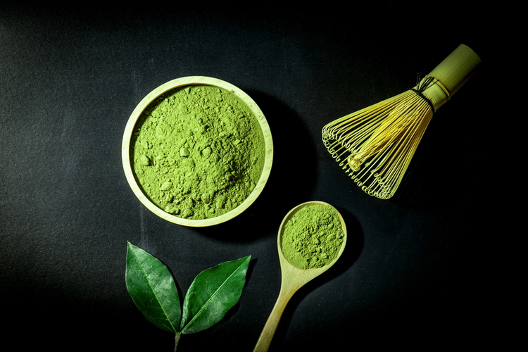 Matcha powder on a spoon and wooden bowl with the matcha leaf and whisk.
