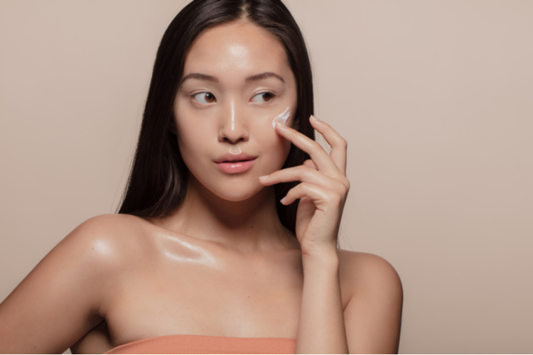 Woman applying loum beauty of calm to her face over beige background.
