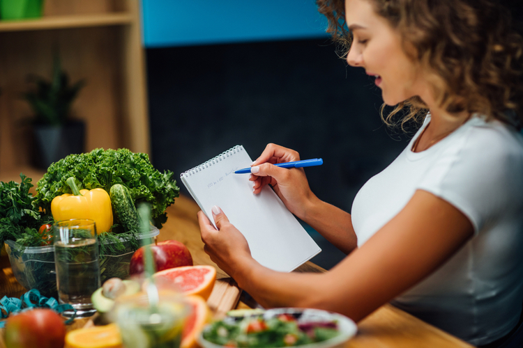 Woman writing diet plan on table and using vegetables.