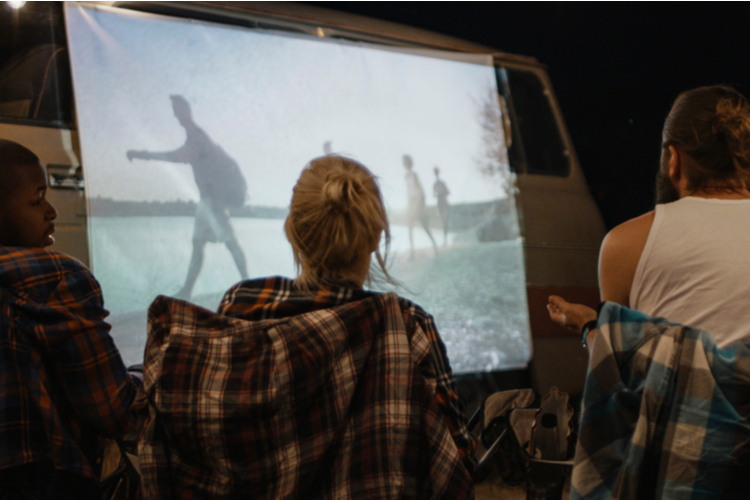 Family having fun and relaxing while watching movie on screen on van in night time as part of things to do for father's day.