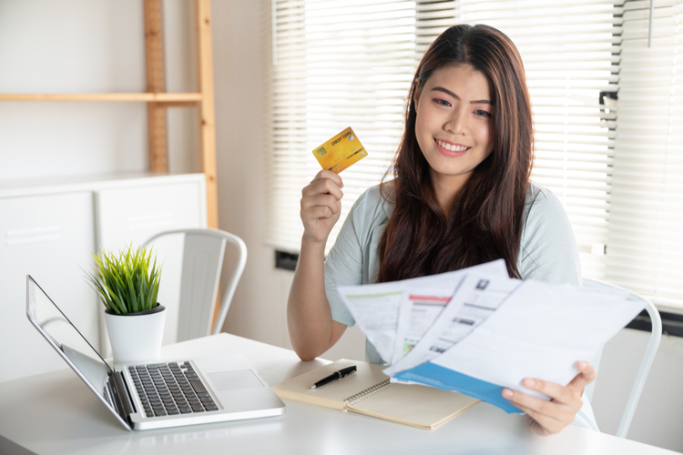 Woman smiling holding so many expenses bills such as electricity bill.
