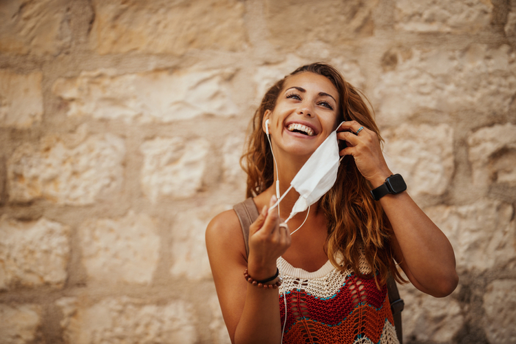 Shot of a happy young woman removing protective mask.