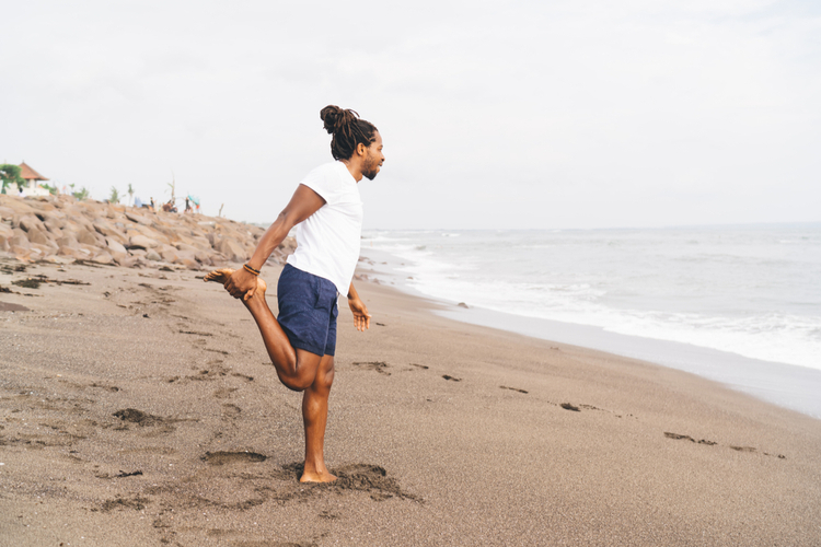 Male in activewear doing stretching exercise for legs while training on beach.