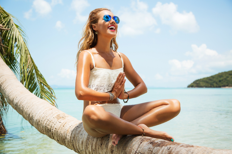 Summer lifestyle portrait of pretty happy young girl with tanned body knowing how to improve emotional health doing yoga at the beach.