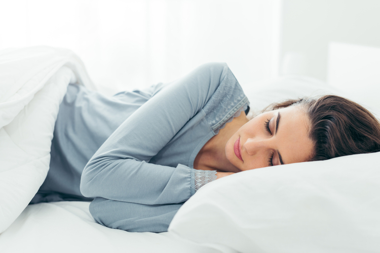 Woman sleeping in her bed and relaxing in the morning.