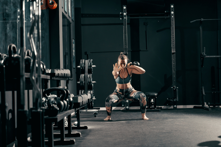 Woman with earphones doing workouts with kettlebell in squat position barefoot training.