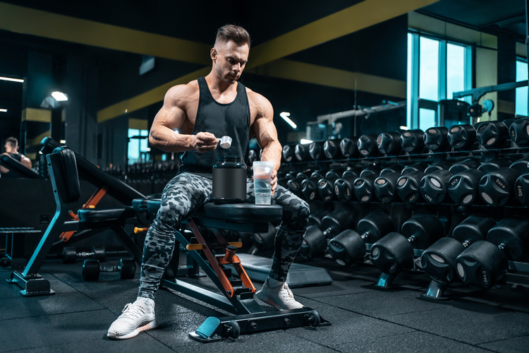 Man preparing supplements before a workout session.