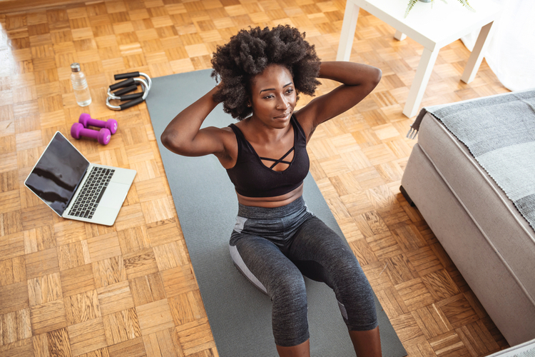 Young fit woman in black sportswear is doing sit-ups at home for spot fat reduction on her abdomen.