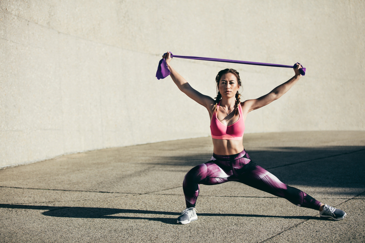 Portrait of muscular woman in sportswear exercises with resistance band. Fitness female model doing stretching workout.