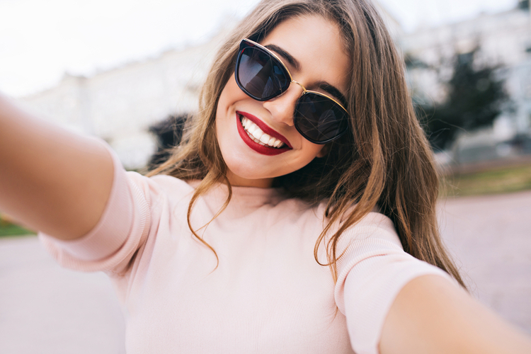 Woman smiling confidently with long hair with sunglasses.