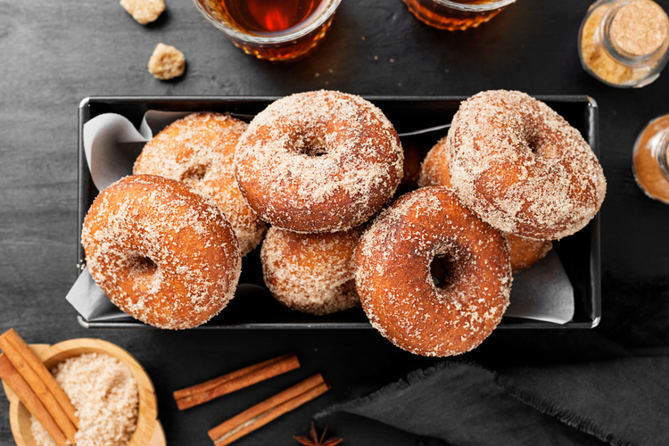 Homemade fresh fried donuts frosted with cinnamon and sugar.