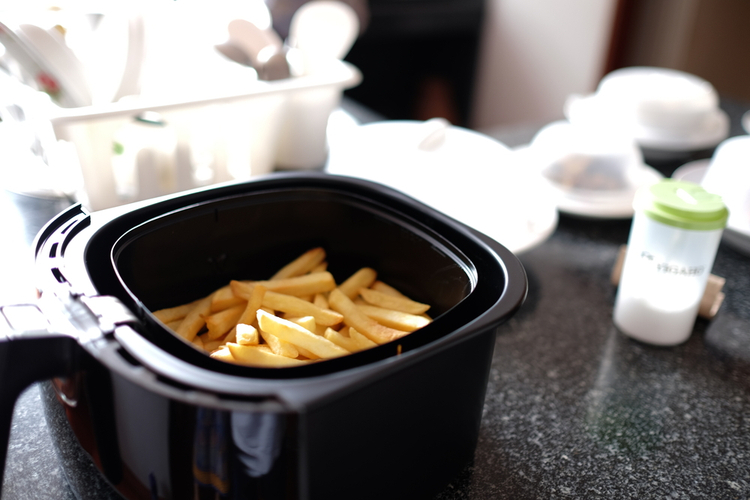 Home-made french fries in modern air fryer.
