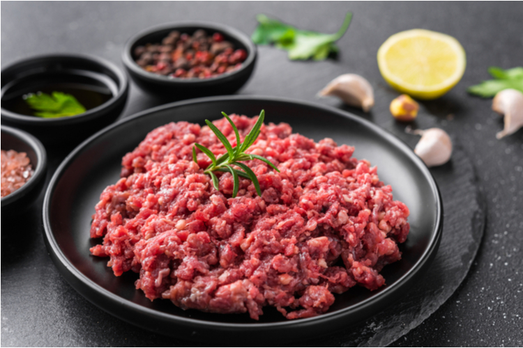 Ground beef on a black plate against stone background.