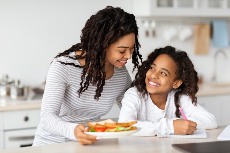 Cute black mother and daughter eating sandwiches at kitchen.