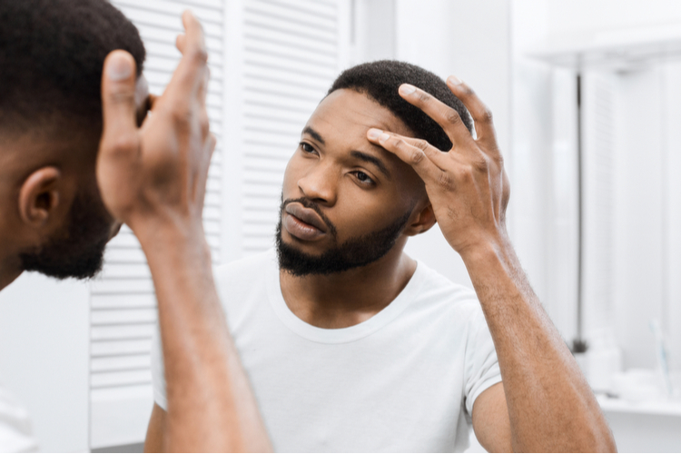 Man touching his face, looking herself in mirror in bathroom.