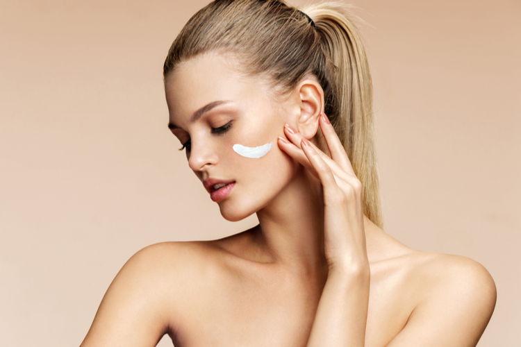 Woman applying cream on her face knowing what is NAD and how it works.