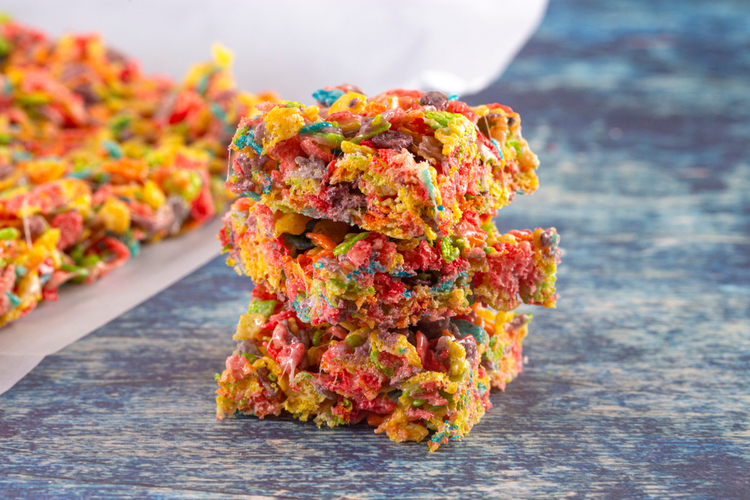Fruity pebbles protein cheesecake frosting cereal treat bars on blue table.